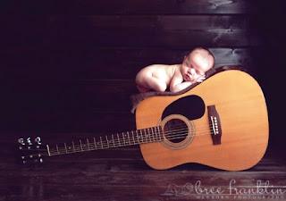 Foto bayi lucu dan imut tidur di atas gitar