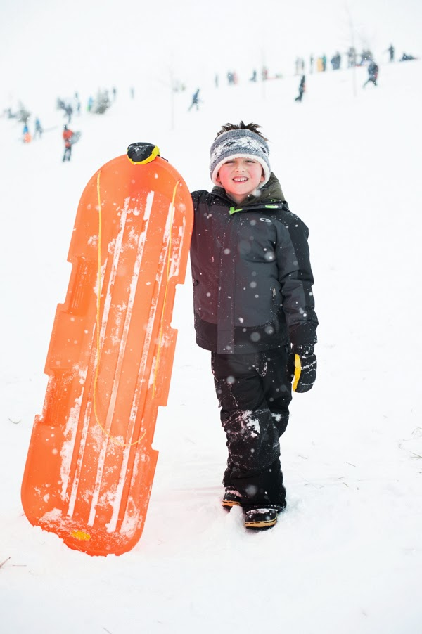 boy smiling while holding his sled upright in the snow