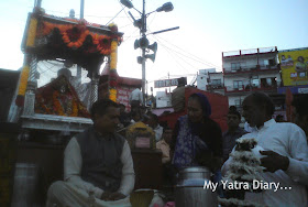 Priests sitting on raised wooden planks and performing certain rituals at the Har Ki Pauri Ghat in Haridwar