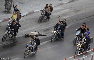 Palestinians drag body of suspected spy behind motorcycles in Gaza