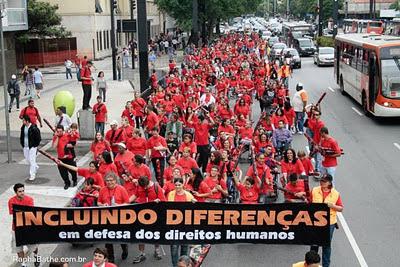 Imagem da oitava Passeata Superação. Na fileira que aparece à frente, seguram uma grande faixa com os dizeres: Incluindo diferenças em defesa dos direitos humanos