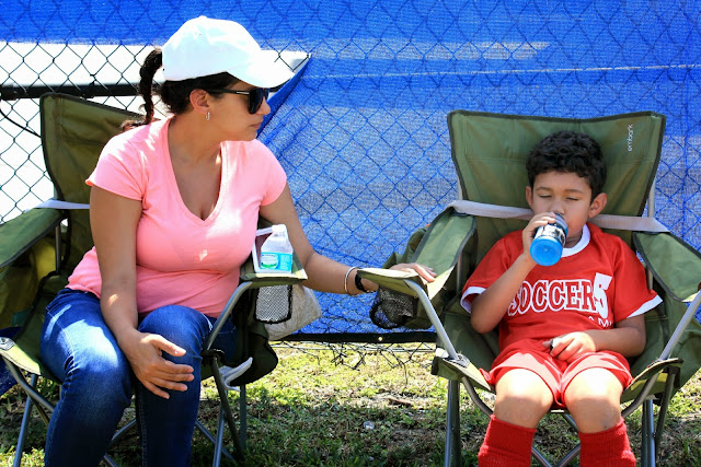 A soccer moms ultimate sideline kit should include quad chairs, a cooler full of goodies like a bowl of fruit, a first aid kit and of course, an extra soccer ball to keep handy for warm-ups and bored siblings!