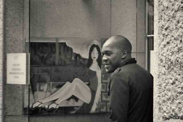 A man stands next to a painting in this Cape Town street photo