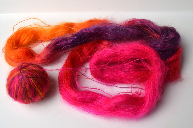 silk mohair in pinks, oranges, and purples, half in a ball, half still in a hank.