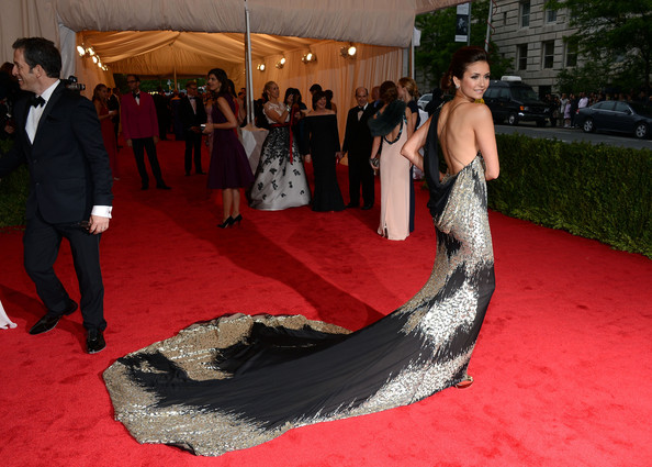 Nina Dobrev in an asymmetrical gold and black backless Donna Karan Atelier gown featuring a dramatic floor-sweeping train at the Costume Institute Benefit Gala 2012 held at The Metropolitan Museum of Art on May 7, 2012 in New York City.