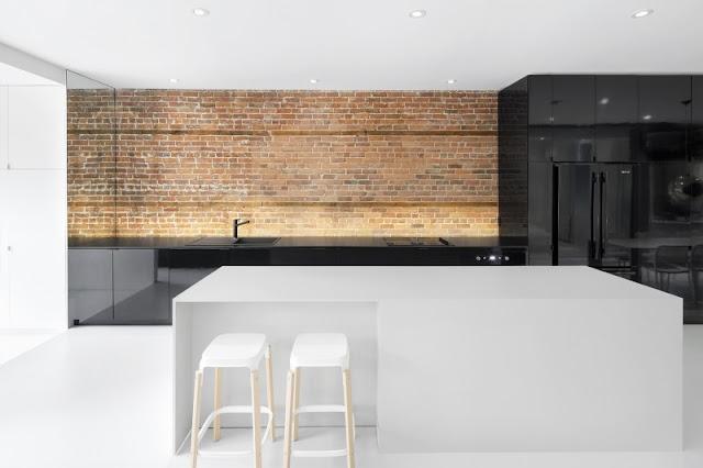 Grande cuisine noir et blanche avec îlot. Noir brillant sur mur de brique.