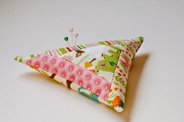 http://www.rileyblakedesigns.com/cutting-corners/2012/03/09/triangular-log-cabin-pincushion-tutorial/