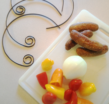 Image of ingredients for Sausage Kabobs. Circle kabobs are along side the cutting board with meat and vegetables.