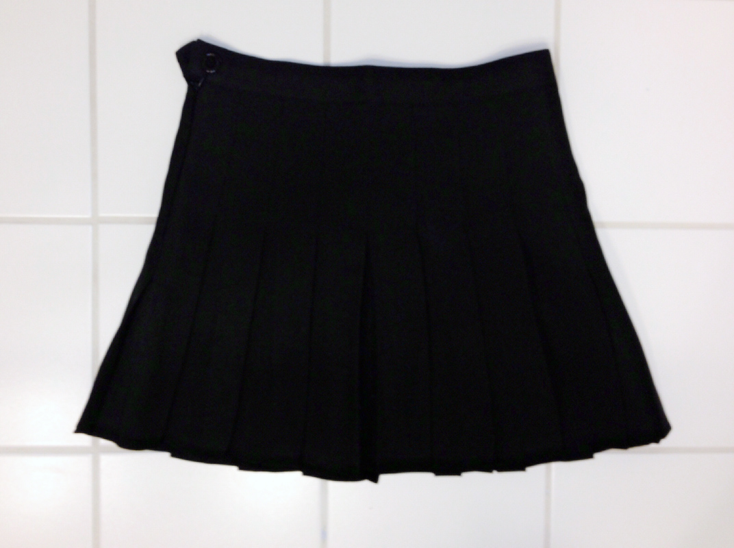 The black pleated high-waist tennis skirt from SheInside, similar to American Apparel's schoolgirl tennis skirts.