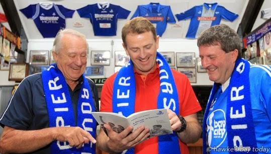 "L-R: Barrie Hughes, president, Phil Purvis, ex-player, Terry Parkin, life-member, Napier City Rovers, looking through ""A Decade of Success 1983-1992"", at their Bluewater Stadium clubrooms, Park Island, Napier. photograph"