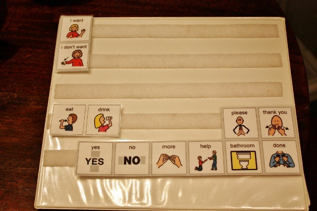 Laminated folder with laminated squares representing various things a person might like to communicate, like