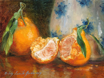 Open tangerines by antique blue and white pitcher