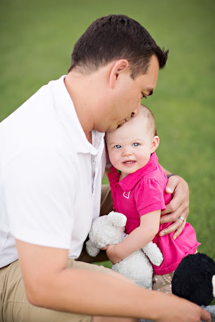 Father snuggles his baby girl during photo shoot