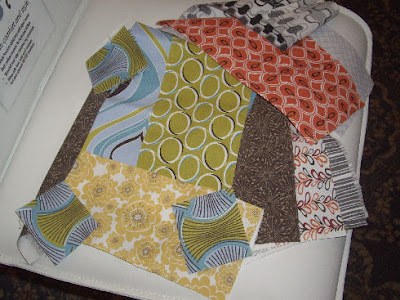 photo of a selection of scrap fabric pieces, each with strong contrast colours and geometric shapes.