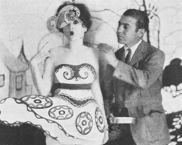 Artist is painting design onto the costume of actress for photo shoot 1926