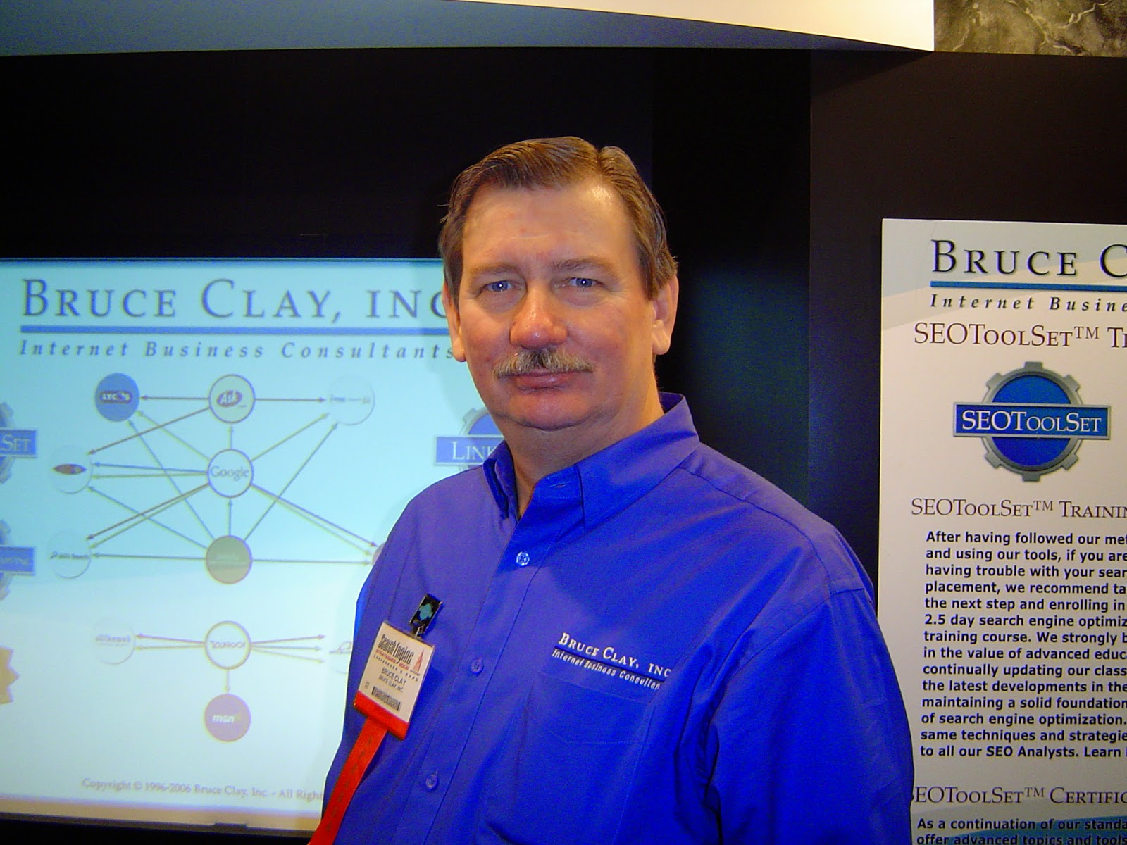 Bruce Clay standing in front of a presentation made by his company:  Bruce Clay, Inc.