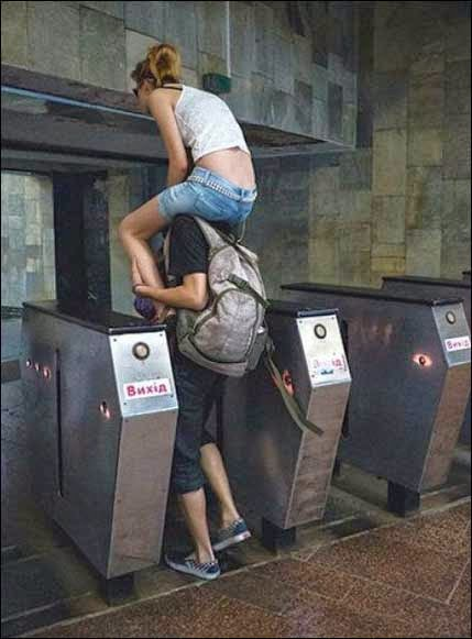 فتى يحمل صديقته على اكتافه ويعبر بها ماكينة التذاكر