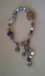 A bracelet with many different size, shape, and color beads. Some of the larger, more eye-catching beads are a dark blue one with filigree metal work on both ends, an oval bead in different shades of gray that looks like a small stone, a round brown bead that might be glass, and a diamond-shaped bead that hangs like a charm off the bracelet. There are several small accent beads, many of them a shimmery silver color or pearl-type bead. At the end where the clasp is, near the diamond-shaped bead is, are four short strands of beaded dangles of different lengths.