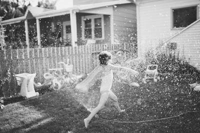 Foto de niña jugando en el patio con la manguera
