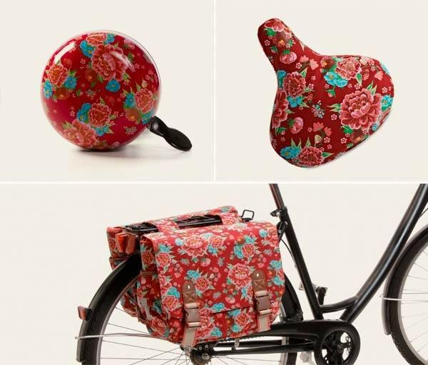 Complementos en color rojo y estampado de gardenias, para bicicleta urbana negra.