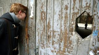 """Cattelan đã tạo được hiệu quả tương tự ở khu Warsaw Ghetto, nơi bức tượng có thể nhìn thấy qua một lỗ trên chiếc cổng bằng gỗ. Cattelan làm việc và sinh sống tại New York được đánh giá là nghệ sĩ châm biếm nổi tiếng khi tạo ra một vụ tranh cãi khác không kém phần gay gắt tại Warsaw khi tạo ra tác phẩm hình nộm Giáo hoàng John Paul II đang bị một thiên thạch đè nát. Tác phẩm có tên """"La Nona Ora"""" hay """"Giờ thứ Chín"""" cũng được đem đi triển lãm tại Ba Lan, một quốc gia có rất đông tín đồ Thiên Chúa sinh sống."""