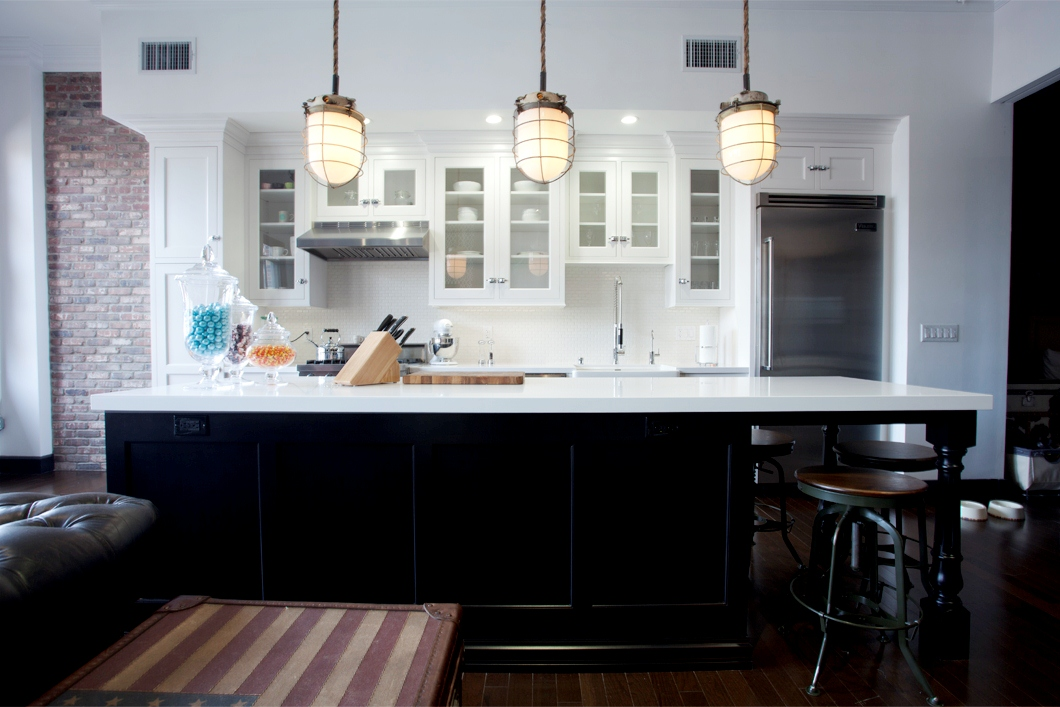 lights, dark black island, quartz counter tops, white kitchen cabinets