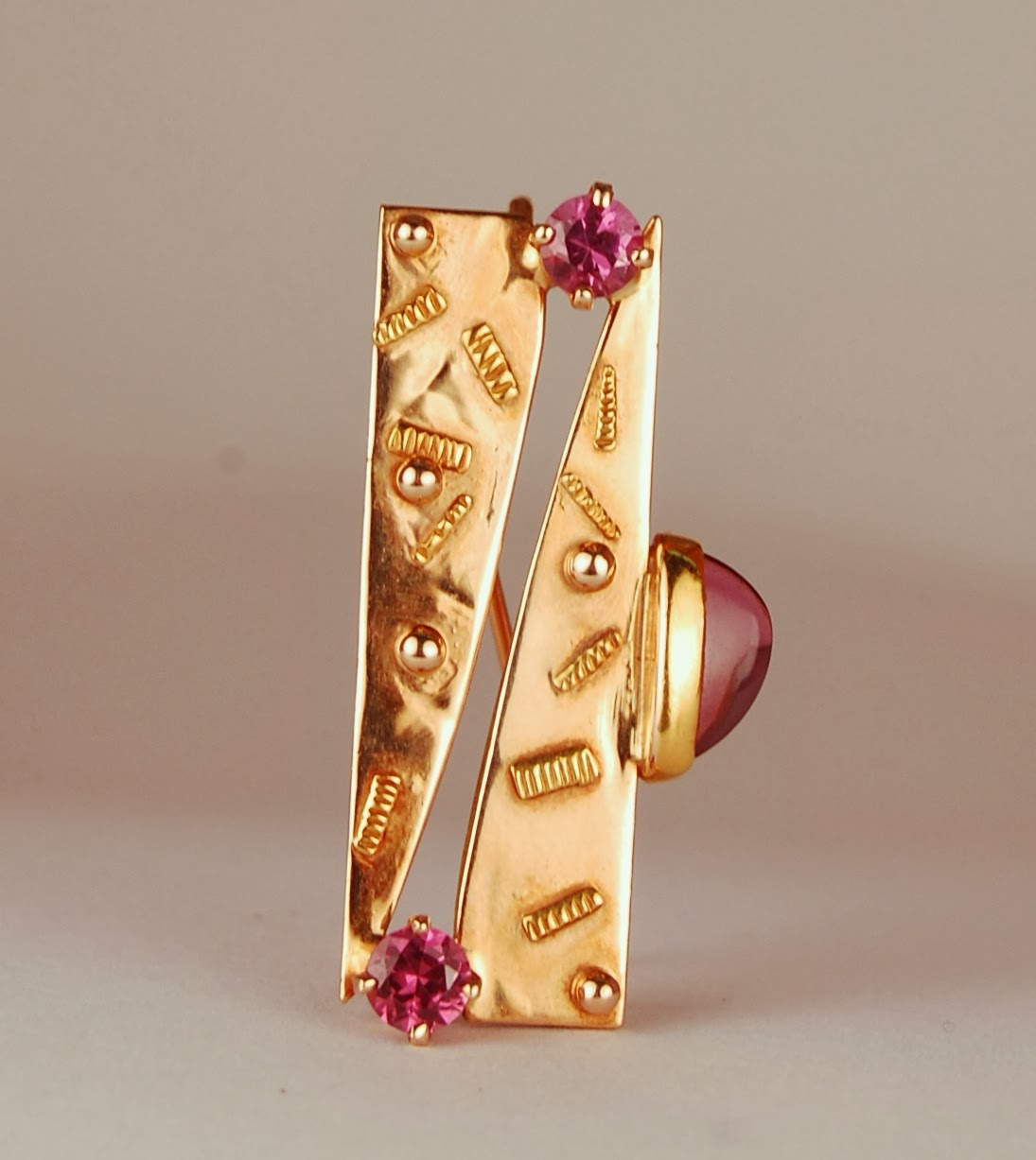 yellow gold rectangular pin with purplish garnets