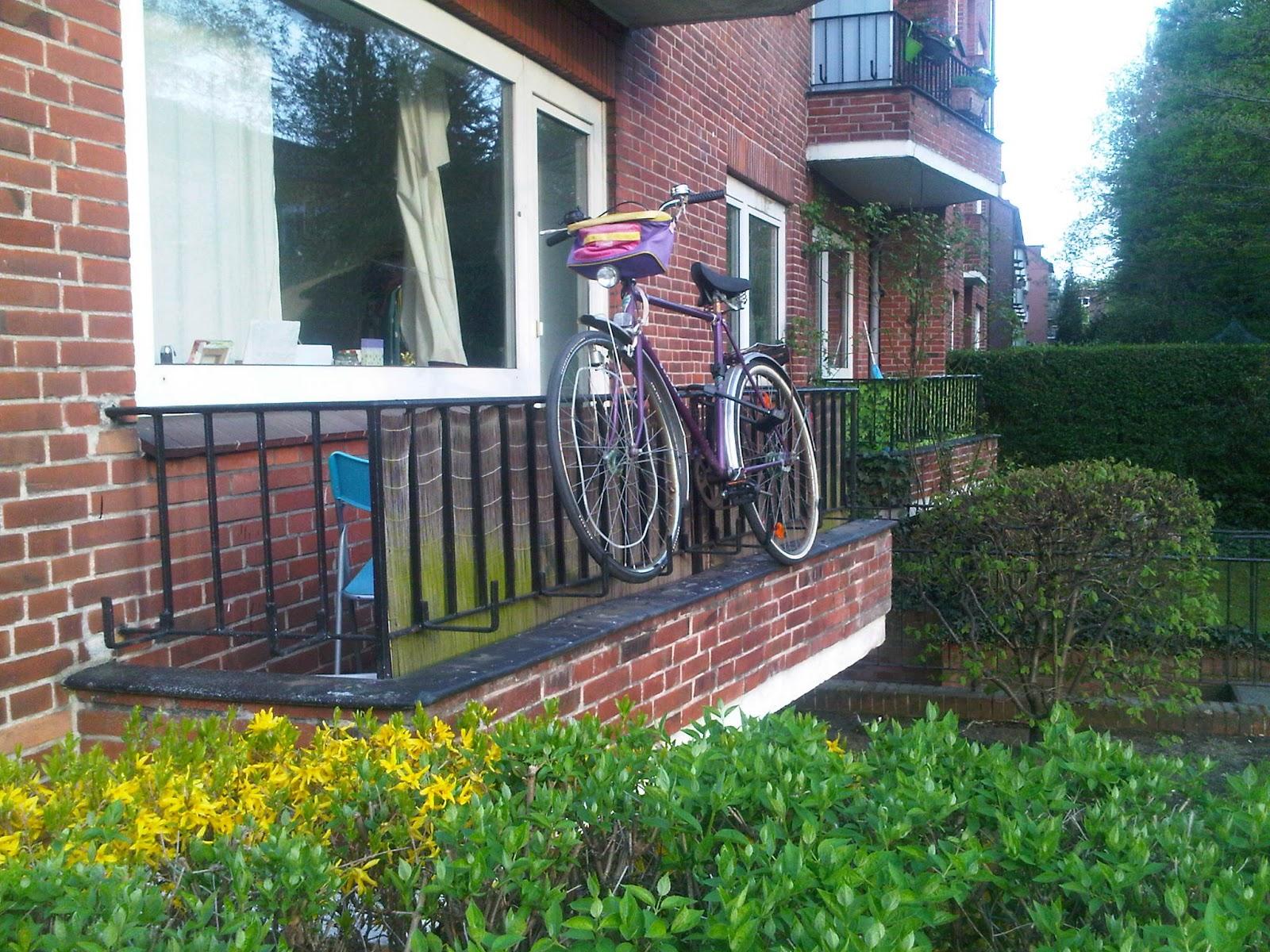 Fahrrad am Balkon aufgehängt. Ein Rad außen am Balkon aufgehängt und abgeschlossen.