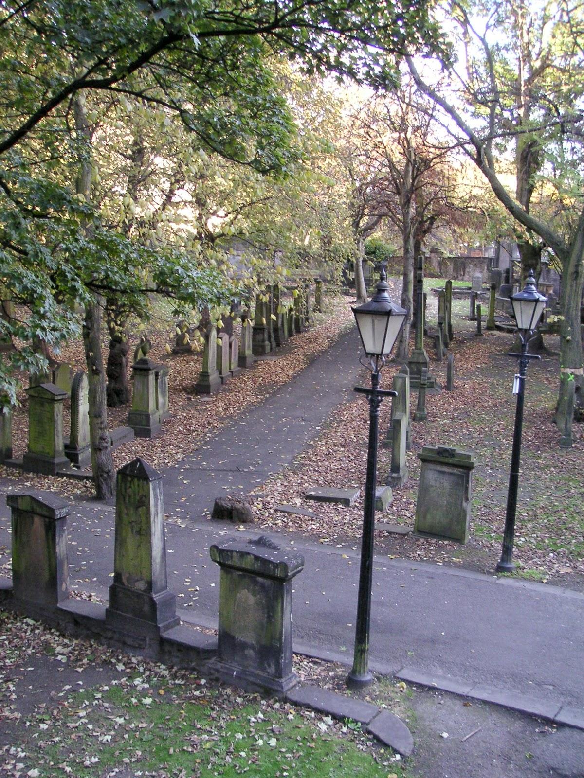 Blick von oben auf einen Friedhof mit vielen laubbedeckten Gräbern und Steingrabsteinen