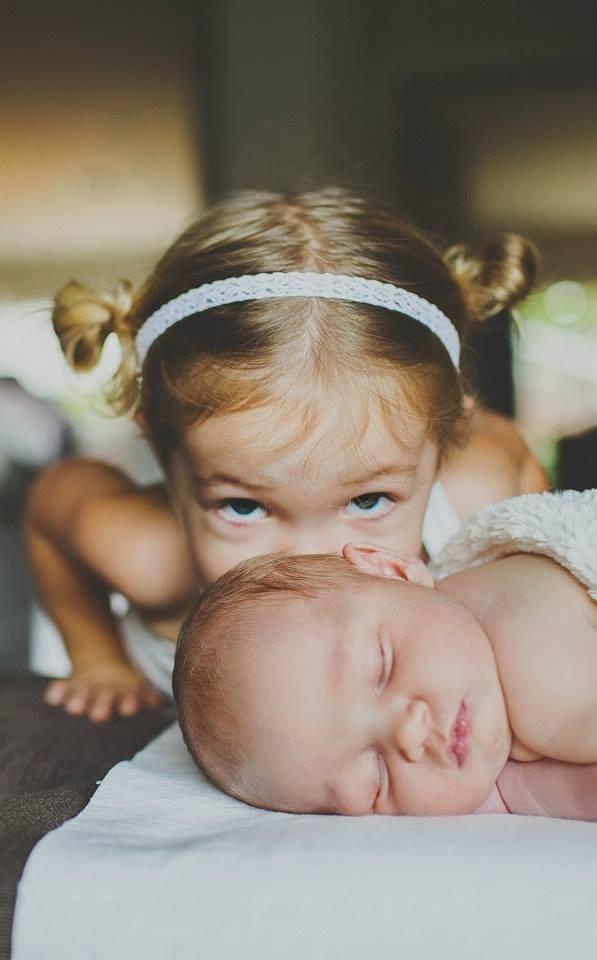 cute girl kissing a baby