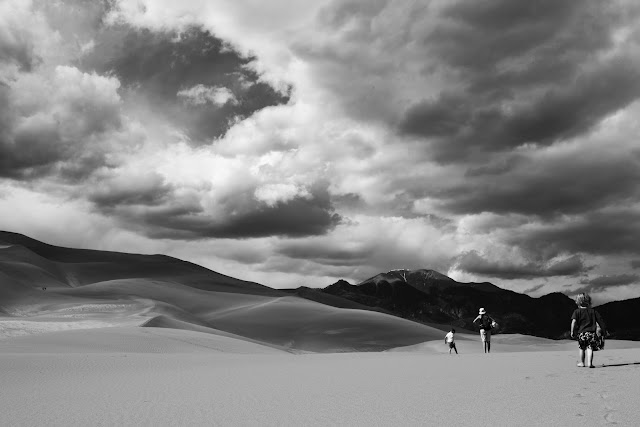 Big clouds over hikers at Great Sand Dunes in Colorado.