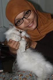 Foto gadis manis berkerudung dengan kucing kesayangannya