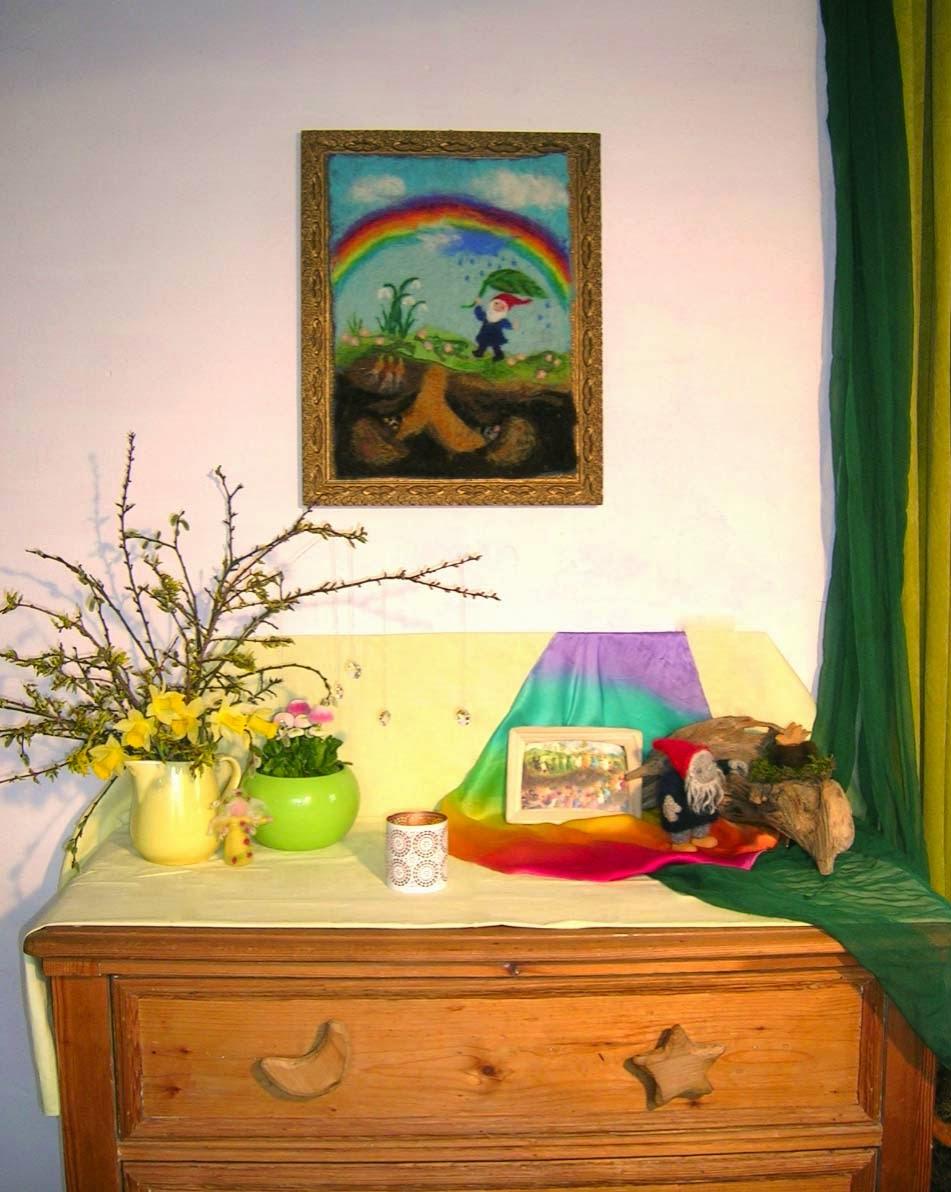 Jahreszeitentisch im April, Regenbogentuch, Frühlingsblumen, Wurzelkinder, Zwerg im April, Zwerg mit Regenbogen, Waldorfkindergarten, Wollbild mit Regenbogen, Filzbild mit Zwerg, Jahreszeiten Waldorf