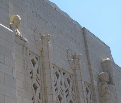 White exterior above the west doors, engraved Omaha Union Station, with two flanking sculptural figures