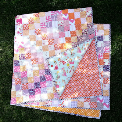 a pink, orange, and purple folded patchwork quilt
