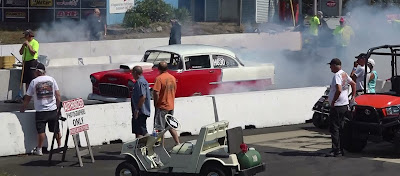 Red and white 55 Chevy Belair drag racer performs burnout in waterbox
