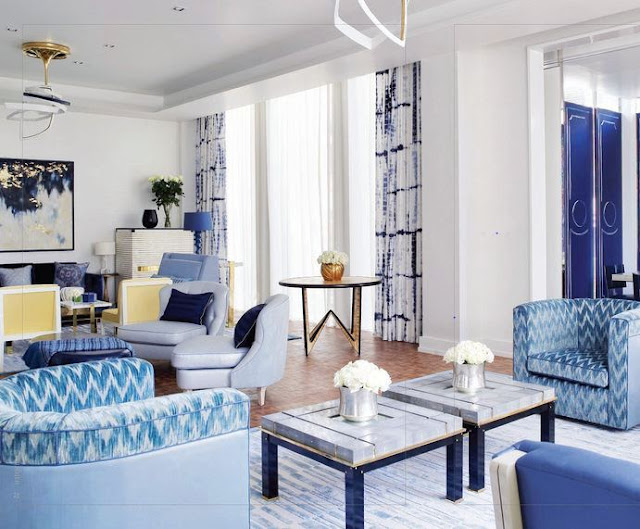 living room in bangkok with blue and white chevron printed armchairs,  lacquer doors, a wood floor, floor length blue and white tie dye curtains and marble coffee table