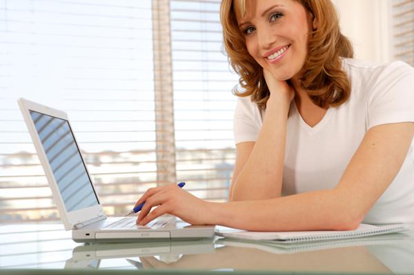 woman writing on computer at home Tujuh Bisnis Online Simpel yang Cocok untuk Wanita