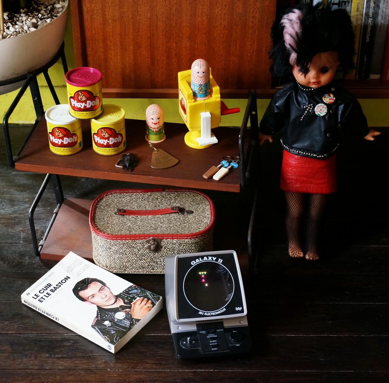 """Brocante sur les terres de Vanessa et John :       une étagère 50s/60s      des boites de pâte à modeler Play-Doh et le coiffeur de 1979      un deuxième exemplaire de """"Le cuir et le baston """" de Maurice Lemoine de 1977      une poupée Clodrey de la collection les Funky de 1983 - 1984 , elle n'avait pas sa jupe ni ses chaussures d'origine,  juste le collant lurex que j'ai remplacé par des résilles et une jupe fait maison à partir d'une vieille ceinture ... davantage streetpunk .     des porte clés , glace Motta et masque africain qui seront prochainement recyclés en broches      une boite à couture     un jeu electronique Galaxy II d' Epoch de 1981 TRES BRUYANT     un porte clé de l'hotel Domino à Pontaillac près de Royan (je suis preneuse de toute info sur cet hotel) 1950 1960 1970 1980 50s 60s 70s 80s punk doll yard sale car boot sale"""