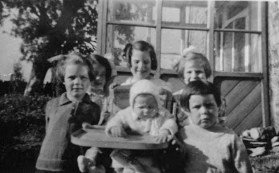 Black and white photo of five girls and a baby outside a stone built house with a half glazed porch.  There is a large tree in the left background.  The baby is sitting in a highchair surrounded by the other girls
