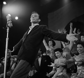 Frank Sinatra on stage backed by showgirls