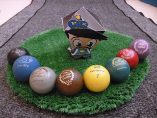 #PKSH2 - Task #4 (Bonus) - The Putter King wobblehead next to 8 different coloured minigolf balls