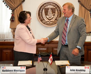 Photo of Canada's John Knubley shaking hands with Kathleen Merrigan USDA