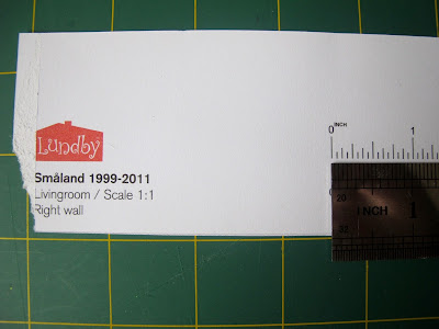 Ruler measuring a guide on a piece of paper printed with 'Lundby Smaland 1999-2001 Livingroom/ Scale 1:1'