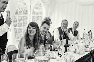 bride smiling during the speeches with natural makeup and loosely waved hairstyle