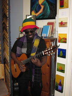 Dark-skinned man with beard, mustache, and sunglasses and a Jamaican knit hat. He is playing an acoustic guitar, one hand on the fret board and the other strumming. He's looking down at the guitar and smiling as if he's having fun.