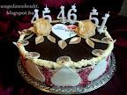 Piros tésztás pezsgőhab torta, tortacsokoládéval bevonva, az oldala színezett kókuszreszelékkel és marcipán szívvel díszítve, felül pedig arany színű ostya virággal és levéllel.