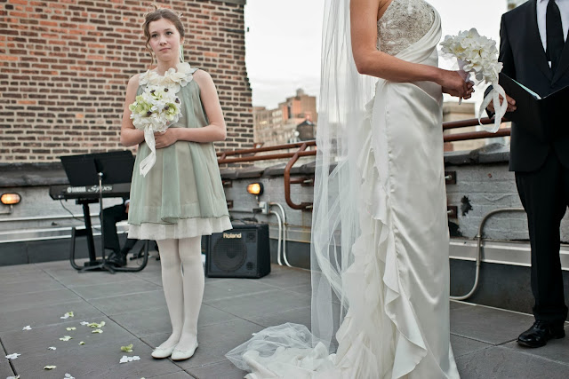 A Model Wedding, niece bridesmaid holds flowers at rooftop wedding