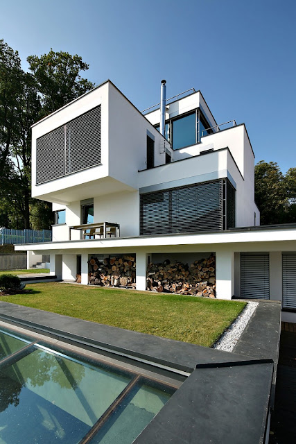 Home with White Concrete Wall and Black Blind Windows Made from Wooden Material