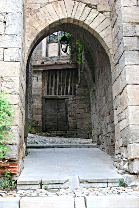 massive stone archway with wooden house door seen through it